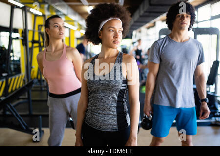 Group of young people training in gym - Stock Image