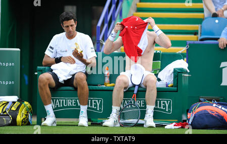 Eastbourne, UK. 25th June, 2019. Andy Murray of Great Britain has a problem changing his shirt alongside partner Marcelo Melo from Brazil during their doubles match against Juan Sebastien Cabal and Robert Farah of Colombia at the Nature Valley International tennis tournament held at Devonshire Park in Eastbourne . Credit: Simon Dack/Alamy Live News - Stock Image