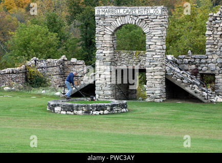Caretaker mowing grass in circular fountain foundation in front of ruins of historic Maribel Hotel - Stock Image