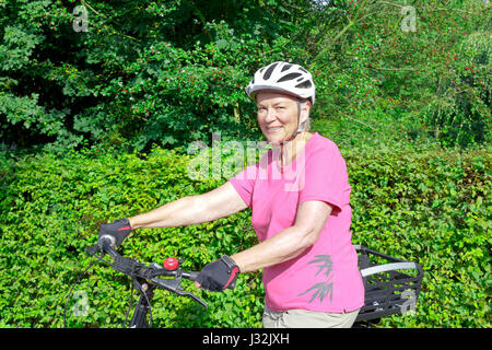 Smiling senior woman with helmet and gloves holding her bicycle on a sunny day, green hedge and bushes in the background, - Stock Image