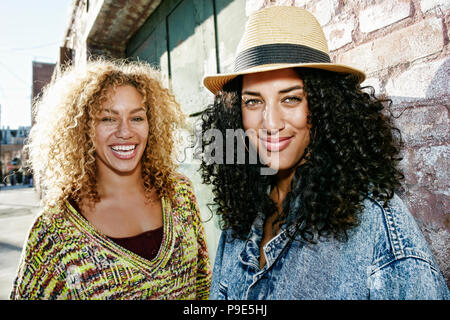 Portrait of two smiling young women with long curly black and blond hair, looking at camera. - Stock Image