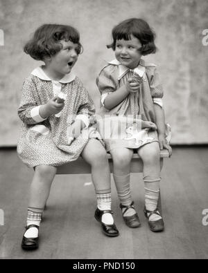 1920s TWO LITTLE GIRLS SITTING ON BENCH EATING ICE CREAM CONES AND TALKING  - f2181 HAR001 HARS COMMUNICATION LAUGH TWIN IDENTICAL DOUBLE PLEASED JOY FEMALES STUDIO SHOT HEALTHINESS HOME LIFE COPY SPACE FRIENDSHIP HALF-LENGTH MATCH SIBLINGS SISTERS EXPRESSIONS B&W BRUNETTE MATCHING SAME HAPPINESS CHEERFUL STYLES AND MARY JANE CONES SIBLING SMILES CONNECTION MARY JANES JOYFUL STYLISH LOOK-ALIKE DUPLICATE FASHIONS JUVENILES LOOK ALIKE TOGETHERNESS BLACK AND WHITE CAUCASIAN ETHNICITY CLONE HAR001 OLD FASHIONED PLAYMATES - Stock Image