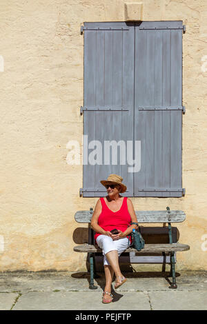Tourist sitting outside a building near Vitrac in the Dordogne in the Nouvelle-Aquitaine region of France. - Stock Image