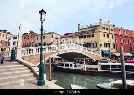 Venice Italy. Passenger boat passing under Canaregio bridge. - Stock Image