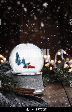 Rustic image of a snow globe with old pick up tuck hauling a Christmas tree surrounded by pine branches, cinnamon sticks and a warm gray scarf. - Stock Image