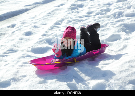 Young Asian girl on sled in snow - Stock Image