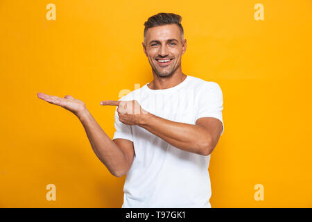 Image of a handsome happy excited man posing isolated over yellow wall background pointing. - Stock Image