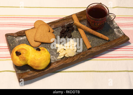 Saffron bread, ginger snaps and Swedish mulled wine or glögg with cinnamon sticks, raisins and sliced almonds - Stock Image