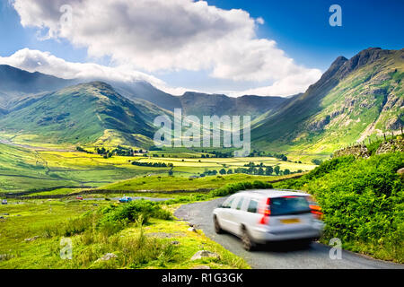 Car in motion on a countryside road above Great Langdale valley, with a stunning view over the Lake District hills, UK - Stock Image