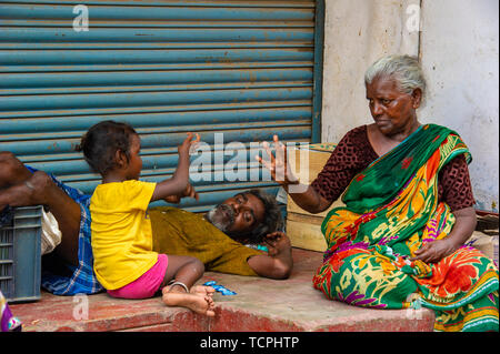 Poverty in Chennai, India, where three generations of a family play a game together - Stock Image