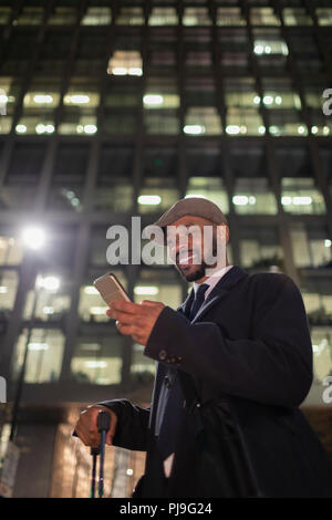 Smiling businessman with smart phone standing below highrise building at night - Stock Image
