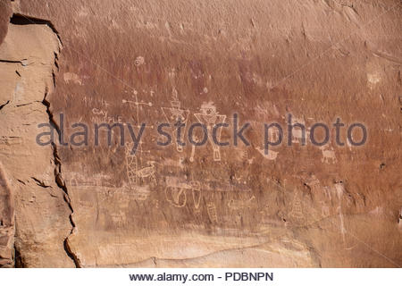 Fremont petroglyphs recorded over older and very faint Barrier Canyon style pictographs. - Stock Image