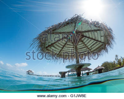 Eating table and sunshade installed directly in the calm waters of Fakarava lagoon at the Pearl Havaiki in French - Stock Image