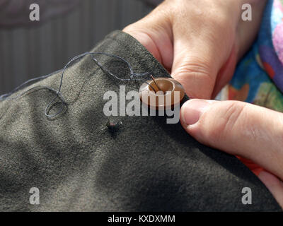 Hand with needle sew on button of dresses - Stock Image