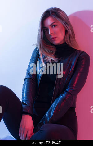Sexy young woman portrait, on colorful background. Seductive brunette model girl in black jacket. Girl sitting down. Red and blue light. Night life - Stock Image