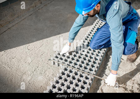 Builder laying paving tiles with holes for grass on the construction site, view from above - Stock Image