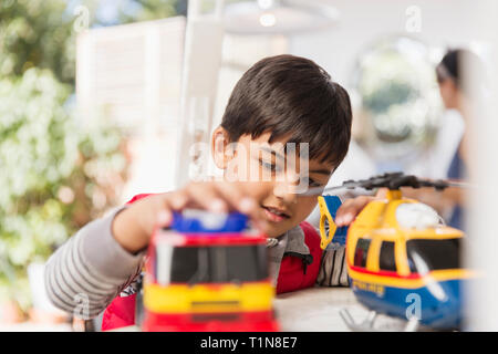 Boy playing with toy helicopter and fire engine - Stock Image
