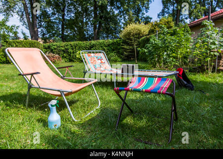 Sunbeds on the grass in a garden with a notebook on the one behind. - Stock Image