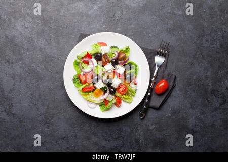 Greek salad with cucumber, tomato, pepper, lettuce, onion, feta cheese and olives, dressed with olive oil. Top view with space for your text - Stock Image