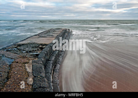 Swirling seawater flows alongside a stone jetty as the waves ebb into the North Sea - Stock Image