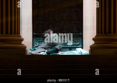 a homeless man wakes early in the morning on the steps of a library - Stock Image