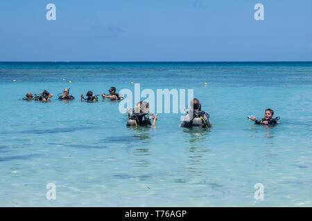 Divers in full SCUBA gear prepare for a dive off the shore of West Bay Roatan Honduras. - Stock Image