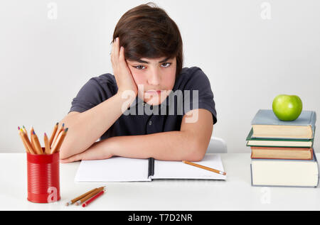 Unhappy and depressed caucasian student boy is feeling confused and angry while doing his homework - Stock Image