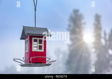 FLODA, SWEDEN - NOVEMBER 27 2018: Small red typical Swedish house style bird house feeder against beautiful out of focus winter background - Stock Image