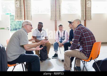 Men talking and listening in group therapy - Stock Image