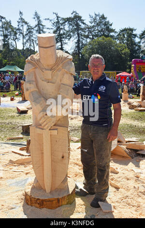 Tim Burgess alongside his carved Knight at the Scottish Chainsaw Carving competition, held on Saturday 2nd September at Cartridge, Inverness-shire. - Stock Image