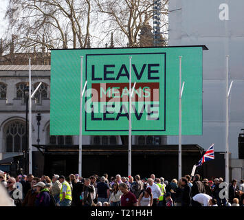 A giant screen displays a message 'Leave means Leave', in Parliament square, as part of a large Pro-Brexit demonstration. - Stock Image