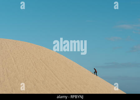 young adult asian male climbing a sand dune against blu sky background. concept of traveler, effort and nature - Stock Image