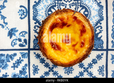 A Single Pastel de Nata On Traditional Blue And White Azulejo Tile Towel Background - Stock Image