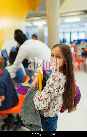 Portrait smiling, confident junior high girl student carrying books - Stock Image