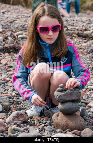 Dunbar, East Lothian, Scotland, UK. 21st Apr 2019. European stone stacking championship: A girl balances stones in the Quantity competition for children under 15 years of age –- most stones balanced vertically - at Eye Cave beach on the second day which comprises 2 competitions, a 3 hour artistic challenge and a children's competition. The overall winner receives a trip to llano Earth Art Festival & World Stone Balancing competition in Texas in 2020. Credit: Sally Anderson/Alamy Live News - Stock Image