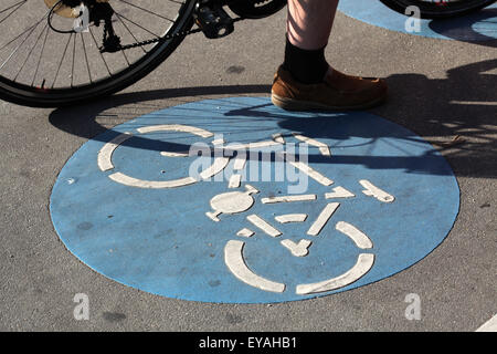 Biker stands next to a blue bike way sign in Vienna, Austria. - Stock Image