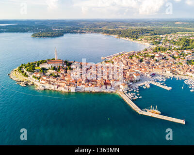 Croatian town of Rovinj on a shore of blue azure turquoise Adriatic Sea, lagoons of Istrian peninsula, Croatia. High bell tower, red tiled roofs of hi - Stock Image