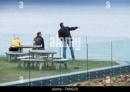 People standing on a balcony overlooking the sea. - Stock Image