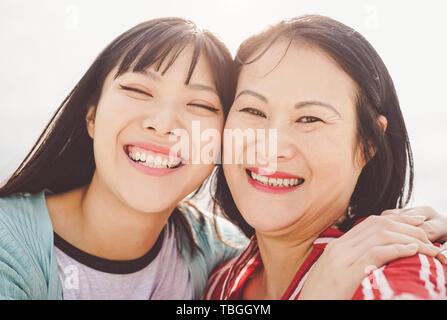 Asian mother and daughter embracing outdoor - Happy Chinese family enjoying time outside - Parenthood, love and people lifestyle concept - Stock Image