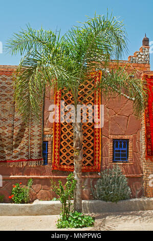 A display of colourful traditioal decorated carpet on a traditional building with palm tree - Stock Image
