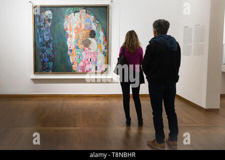Leopold Museum Vienna, rear view of two people looking at Death And Life (Tod Und Leben) by Gustav Klimt inside the Leopold Museum in Vienna, Austria. - Stock Image