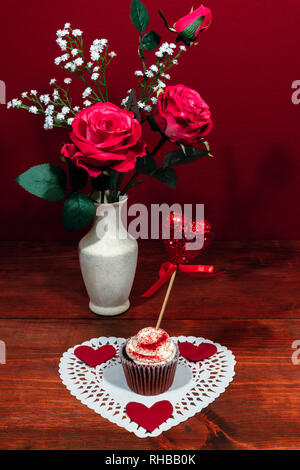 Beautiful pink roses in a vase accented with Baby's Breath flowers, heart shaped white dollie with a decorated cup cake with a heart on a pick. - Stock Image