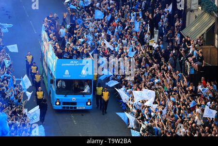 The Manchester City players and staff on the buses pass the crowds of fans gathered on the route during the trophy parade in Manchester. - Stock Image