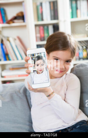Smiling girl showing selfie on cell phone display - Stock Image