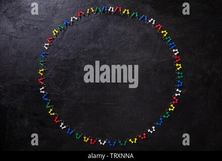 Group of colorful push pins on black background - Stock Image