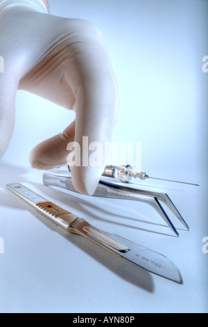 Hand picking up scalpel - Stock Image