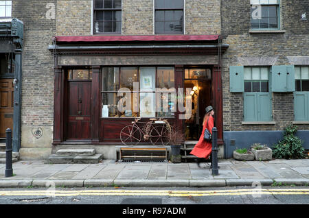 Woman in orange coat walking past antique shop with bicycle on Fournier Street near Spitalfields Market in East End London UK  KATHY DEWITT - Stock Image