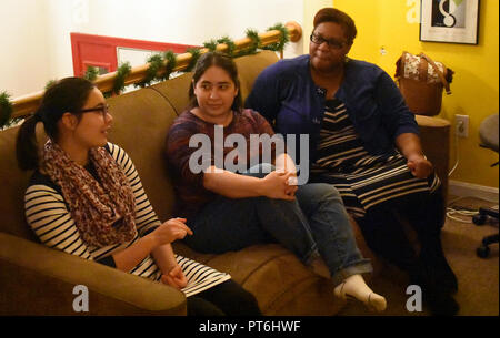 Three women from mixed cultures talking - Stock Image