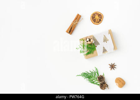 Gift box wrapped in craft paper tied with fabric ribbon pine cones juniper nuts cinnamon on solid white background. New Year presents holiday preparat - Stock Image