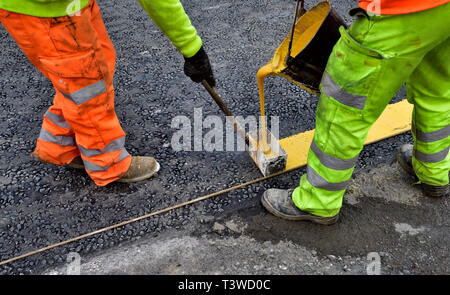 Workman putting in yellow road markings with hot melt paint - Stock Image